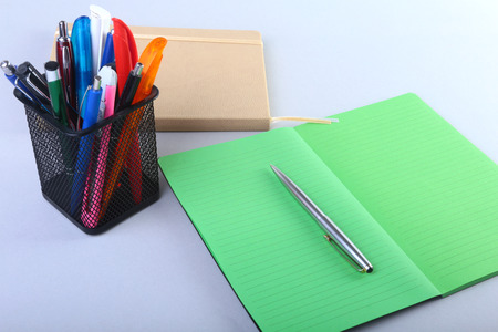 office stapler: Colorful notebooks and office supplies on white table. Stock Photo