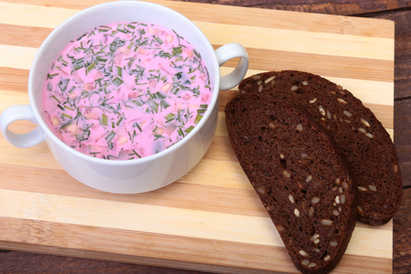 cold: Popular spring cold soup okroshka with yoghurt. Okroshka in a bowl and slices bread on wooden table. Selective focus Stock Photo