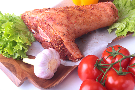 Raw pork knuckle and vegetables, garlic, tomatoes, bell pepper. spices and lettuce leaves on a cutting board. Selective focus. Ready for cooking. Stock Photo
