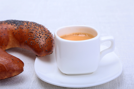 Classic espresso in white cup with cake on white background.