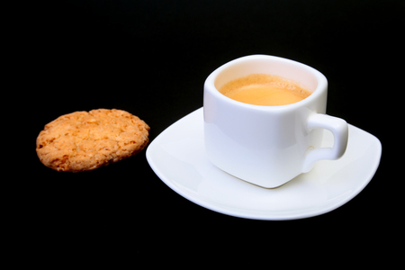 Classic espresso in white cup with homemade cake on black background. Selective focus. Stock Photo
