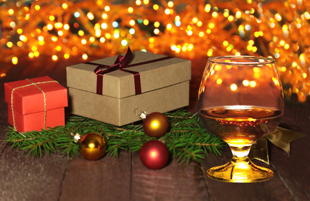 glass with cognac or whiskey, gift box, colored balls and christmas tree on wooden table. Celebrities composition. Selective focus.