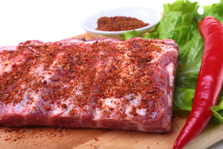 Raw pork ribs with herbs and spices on wooden board. Ready for cooking.