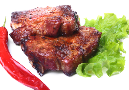Steak of grilled meat and chili pepper with tomato, lettuce leaves on white plate.