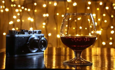 Glass of brandy or cognac and retro camera on the wooden table Stock Photo