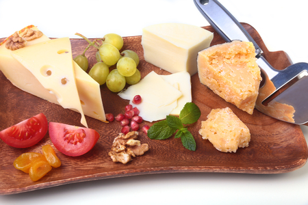 Assortment of cheese with fruits, grapes, nuts and cheese knife on a wooden serving tray Stock Photo