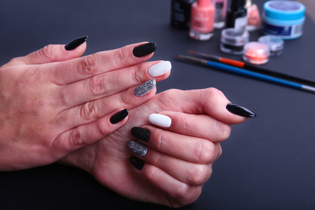 Black, white Nail art manicure. Holiday style bright Manicure with sparkles. Bottle of Nail Polish. Beauty hands. Stylish Nails, Nail Polish Stock Photo