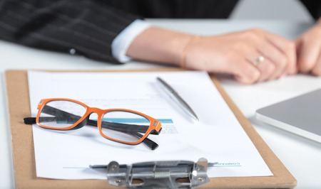 Closeup of white desktop with glasses, notepads, pen and other items. Selective focus.