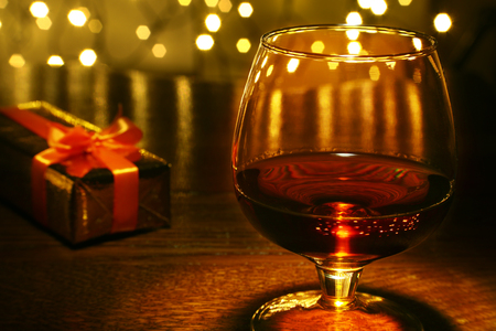 Whiskey, cognac, brandy and gift box on wooden table. Celebration composition on the light background.