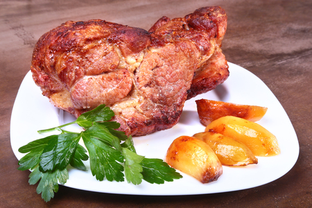 Juicy pork neck chops are grilled with potatoes on a white plate. Stock Photo