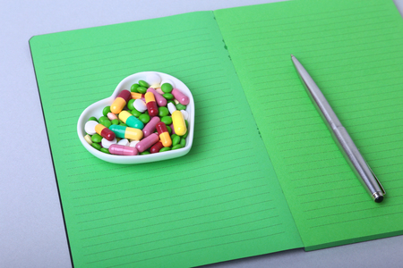 notebook and colorful assortment pills, capsules on plate.