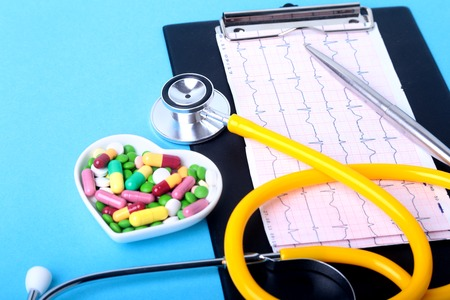 Stethoscope, RX prescription and colorful assortment pills and capsules on plate. Stock Photo