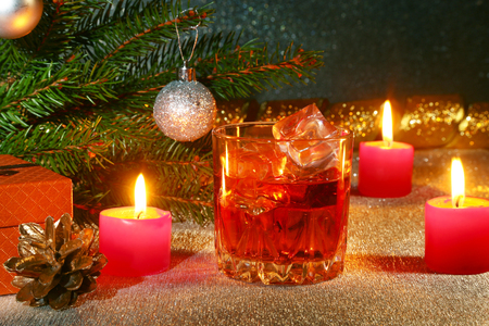 christmas decoration with glass of whiskey or cognac, christmas candles, tree and gift box on a sparkling background. New Year decoration.