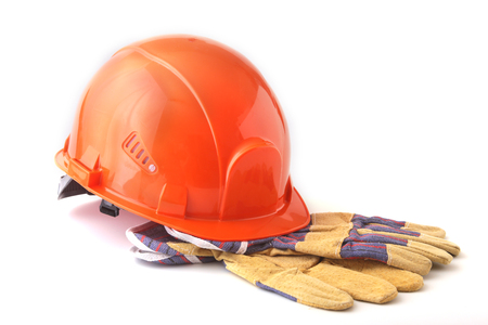 Orange hard hat, safety gloves on white background. Safety helmet. Stock Photo