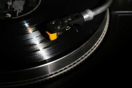 closeup of vinyl turntable, hi-fi headshell cartridge in action, Retro gramophone playing analog disc with music. place for text.