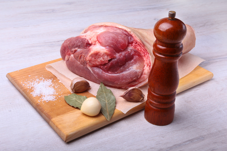 Raw pork knuckle, Aromatic dried bay leaves, garlic, sea salt, pepper grinder and spices on a cutting board. Selective focus. Ready for cooking. Stock Photo