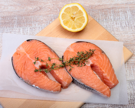 fresh raw salmon with spices and lemon on wooden cutting board. ready for cookin Stock Photo