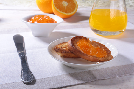 Morning Breakfast set with orange jam on bread toast and juice in glass.