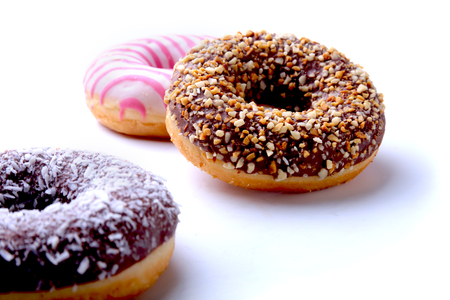 Assorted doughnuts in the glaze, colorful sprinkles and nuts on a white background. Stock fotó