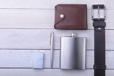Gadgets and accessories for men on light wooden background. Fashionable men s belt, wallet, lighter, Stainless hip flask and pen. 스톡 콘텐츠