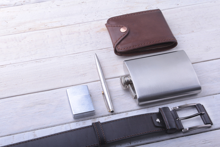 Gadgets and accessories for men on light wooden background. Fashionable men s belt, wallet, lighter, Stainless hip flask and pen. Stok Fotoğraf