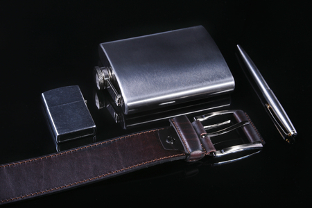 Stainless hip flask, lighter, pen and luxury belt isolated on mirror black background.