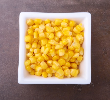 Sweet canned corn in white bowl. Ingredients for salad. Selective focus. Stockfoto