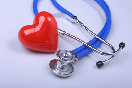 Stethoscope and red heart on white table with space for text.
