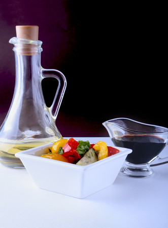 fresh vegetable salad with tomato, cucumber, bell pepper, lettuce leaf in white bowl, olive oil and balsamic souce in bottle. Selective focus.