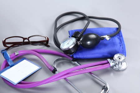 stethoscope, Red heart, glasses and blood pressure meter on white background. Selective focus.