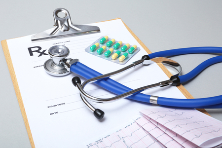 Stethoscope, red heart, RX prescription and assorted pills on white table with space for text. Stock Photo