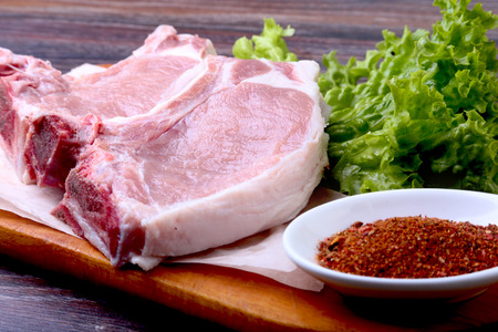Raw pork steak with spices Leaves lettuce on wooden cutting board. Ready for cooking. Stock Photo
