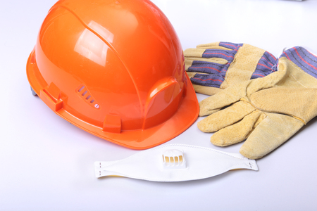 Orange hard hat, goggles, protective mask, respirator and safety gloves on a white background. Stock Photo