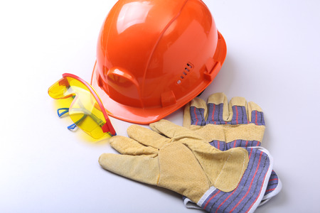 Orange hard hat, goggles and safety gloves on a white background. Archivio Fotografico