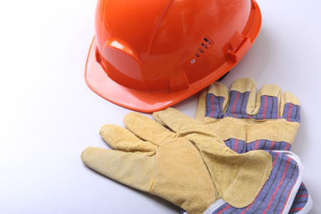Orange hard hat, goggles and safety gloves on a white background. Stock Photo