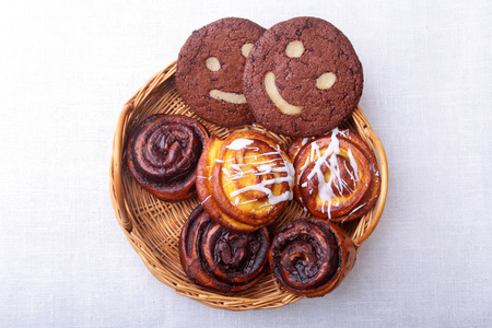 Freshly baked homemade sweet rolls with cinnamon, oatmeal cookies in a wicker basket. Healthy Food Snack Concept. Copy space.