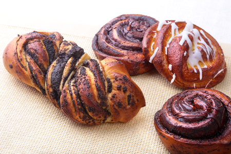 Freshly baked homemade sweet rolls with cinnamon on white background. Healthy Food Snack Concept. Copy space.