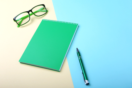Business accessories on desktop: notebook, diary, fountain pen, glasses. Macro with blur and soft focus. Stock Photo