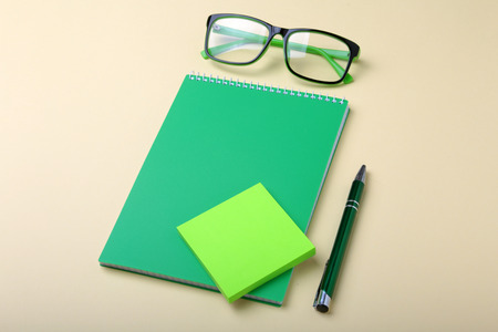 Business accessories on desktop: notebook, diary, fountain pen, glasses. Macro with blur and soft focus. 写真素材