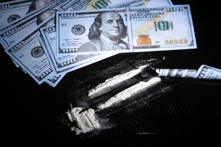 Cocaine drugs heap still life on a mirror with rolled 100 dollar banknote, closeup view. Stock Photo
