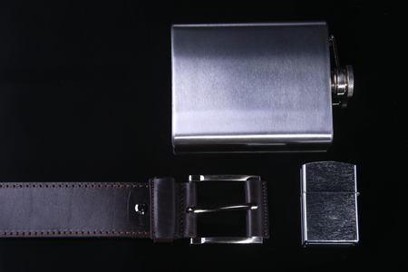 Stainless hip flask, lighter and luxury belt isolated on mirror black background.