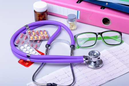 Medical stethoscope lying on cardiogram chart with pile of pills closeup. Cardiology care, health, protection, prevention and help. Healthy life or insurance concept 写真素材