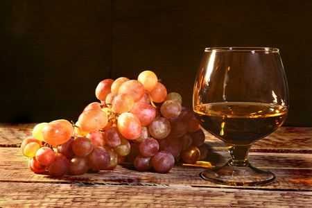 Cognac or Brandy in a glass and fresh grapes, still life in rustic style, vintage wooden background, selective focus. 写真素材
