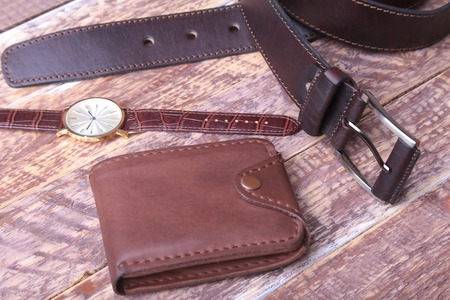 Mens accessories with brown leather wallet, belt and watch. Фото со стока