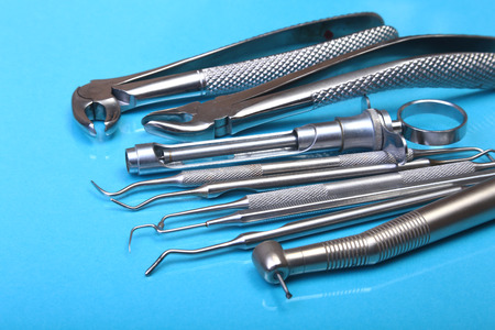 Set of metal medical equipment tools for teeth dental care on blue background. Selective focus.