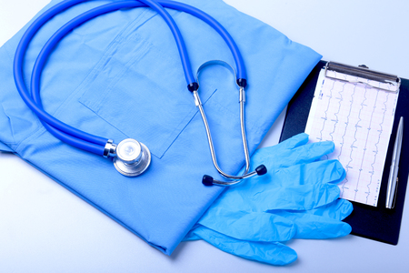 Medical stethoscope, gloves, RX prescription, and blue doctor uniform closeup. Medical help or insurance concept. Cardiology care, health, protection and prevention. Stock Photo