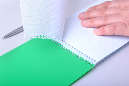 hands wresting the sheet of paper out of a spiral notebook. Reklamní fotografie