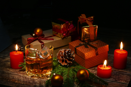 Cognac or whiskey in glass. Christmas balls, gift boxes and candles. New Year's tree, balls and glass with alcohol