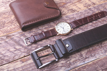 Set of men's accessories for the business with leather belt, wallet, watch and smoking pipe on a wooden background. The concept of fashion and travel