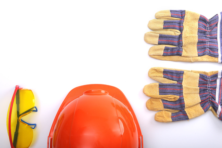 Orange hard hat, leather work gloves and safety glasses on a white background